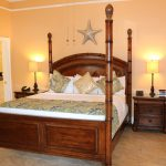 Large bed with bedpost frame at Southernmost Point Guesthouse