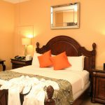 Queen Bed with Bright Pillows and bathrobes at the Southernmost Point Guesthouse