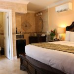 King size bed with six fluffy pillows with attached bathroom at Southernmost Point Guesthouse